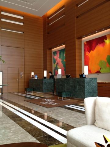 シェラトングランドホテル広島 広島駅前に隣接するビル五階にある、こぢんまりしたフロントロビー。窓が大きく明るいのは好印象。でもエレベーターを降りた目の前が、オープンフロアのレストラン。すぐ側にフロントという落ち着かない作りでした。