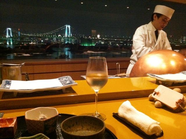 ヒルトン東京お台場 ホテル内にあるレストラン 天麩羅 吉野では、目の前で料理してくれる揚げたての天麩羅がいただけます。ゆったりとしたカウンターの向こう側には大きな窓があり、レインボーブリッジと東京の夜景が美しい。